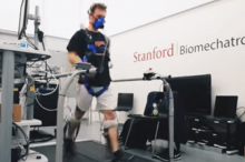 """Video screenshot showing a male volunteer wearing ankle exoskeleton devices on a large mechanical treadmill, with the words """"Stanford Biomechatronics Lab"""" on the wall behind."""