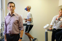 Photo of Dr. Euan Ashley standing at the front of a small room where two subjects, one male and one female, are exercising while wearing multiple kinds of sensors, monitored by a member of the Ashley lab.