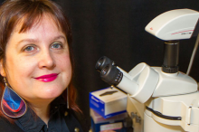 Photo of Dr. Maria Barna in the lab next to a microscope.