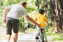 Photo of a father helping his son to learn to ride a bike in a wooded area.