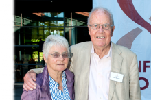 Photo of Bill and Ute Bowes in front of a banner with Stanford Bio-X logo.
