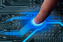 Graphic image of a fingertip being pressed to a circuit board, with circuits lighting up blue.
