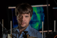 Photo of Dr. Karl Deisseroth in the laboatory, with colorful brain scans in the background.