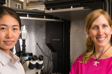 Photo of a young Asian woman and her female Principal Investigator, standing in a specialized lab space with a microscope.