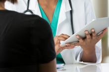 Photo over a female patient's shoulder of a female doctor holding up a clipboard as they talk across a table.