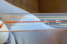 Photo of researcher with gloves on holding up prototype, which looks like a microscope slide with lines on top resembling circuitry, and a channel for blood in the center.