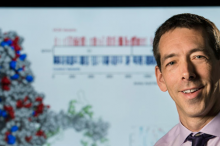 Photo of Dr. Euan Ashley in front of a screen showing a 3D image of a molecule.