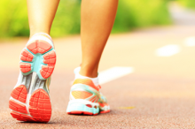 Photo of the feet of a woman wearing athletic sneakers walking down a two-lane path.