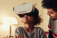 Photo of a young African American girl wearing a VR headset, sitting down with her father.