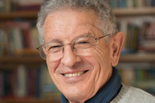 Photo of smiling man in glasses in front of bookshelves.
