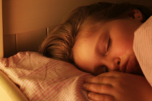 Photo of little girl sleeping in a bed with her hand beside her pillow.