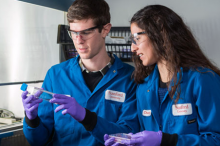 Photo of students Colin McKinlay and Jessica Vargas in the laboratory, examining a test tube and a petri dish near a fume hood.