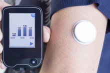 Photo of a woman's arm which bears a glucose monitor, holding up a readout.