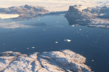 Large body of water in Greenland, broken by islands, with snowmelt visible.
