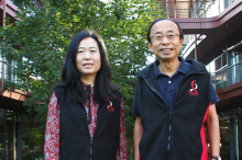 Photo of Drs. Ada Poon and H.-S. Phillip Wong standing in front of the Clark Center wearing fleece vests with the Bio-X logo.