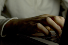 Photo of a man using a computer in the dark, showing only his hand on the keyboard and not his face.