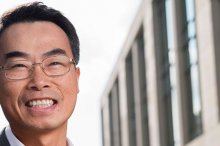 Photo of Dr. Joseph Wu in front of a building with many windows.