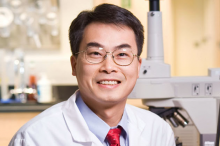 Photo of Dr. Joseph Wu, wearing white coat in laboratory space.