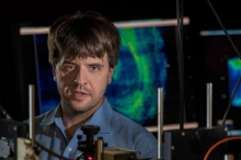 Photo of Dr. Karl Deisseroth in the laboratory, surrounded by equipment with wires and screens displaying brightly-colored optogenetic displays.