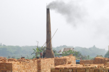 Photo of a tall kiln tower streaming smoke with many huge stacks of orange/red bricks in front of it.