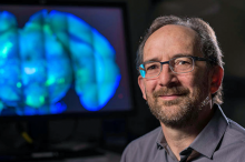 Photo of Dr. Mark Krasnow in lab, next to microscope and in front of a screen displaying a large brain scan image in bright blue.
