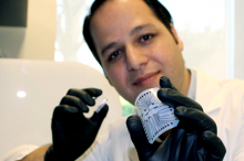 Photo of engineering research associate Rahim Esfandyarpour holding up and flexing small lab on chip device.