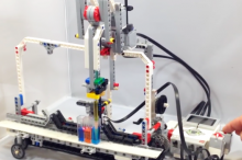 Screnshot from video showing researcher controlling Lego robot with a few button pushes, and robot pipetting liquids in different tubes.