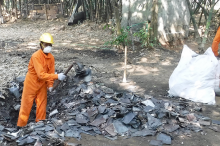 Photo showing two men in orange protective jumpsuits working in a lead waste area, a small pit littered with scraps of metal.