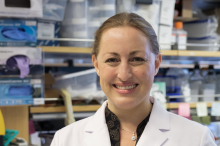 Photo of smiling female faculty member, Dr. Michelle Monje, standing in a wet laboratory space wearing a lab coat. Her blond hair is tied back.
