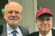 Photo of elder doctor and middle-aged man wearing a red hat.