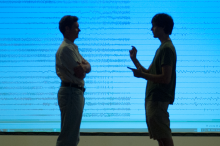 Photo by L.A. Cicero: Professor Chris Chafe and undergraduate researcher Michael Iorga discuss the patterns of brain activity seen in the graphic representation of the seizure as recorded by multiple electrodes.