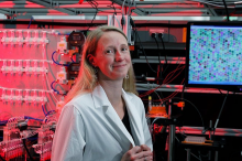 Photo of Dr. Polly Fordyce in the lab, standing in front of a monitor displaying peptide beads.
