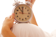 Photo of a pregnant woman lying on her back, holding an old-fashioned alarm clock on top of her stomach.