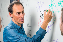 Photo of Dr. Jonathan Pritchard (center) and his colleagues, Yang Li (left) and Evan Boyle, with Pritchard having drawn several interconnecting gene trees and formulas on a whiteboard in different colors.
