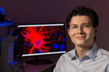 Photo of Dr. Sergiu Pasca in the laboratory, in front of a screen displaying a brain cell.