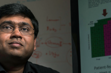Photo of Dr. Nigam Shah with a graph on the projector behind him.