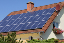 Photo of a house with numerous solar panels on the roof.