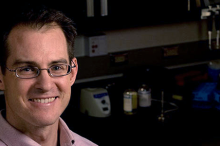 Photo of dark-haired male professor wearing glasses, smiling in lab space with woman pipetting in the background.