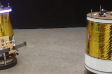 Photo of two of the space robots, which are large cylinders with gold foil around them and a ring of lights at the top.