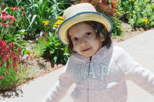 Photo of a little girl walking on a path wearing a hat.
