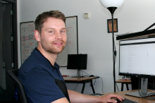 Photo of a white male graduate student wearing a dark blue polo shirt sitting at a beige desk in front of two computer screens. Left screen is white and shows faint lines of code going down the monitor; right screen is black and shows similar lines of code. A whiteboard in the background shows colorful doodles.
