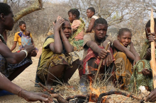 Photo of several members of the Hazda hunter-gatherer tribe in Tanzania crouched around a fire.