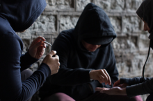 Photo of three adolescents in dark clothes surreptitiously sharing drugs.