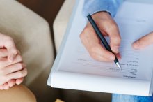 Photo of patient and therapist's hands during a meeting, therapist writing on a clipboard.