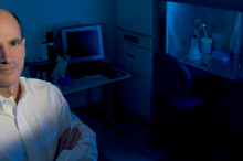 Photo of Dr. Thomas Rando in the laboratory, with fume hood lit up blue in the background.