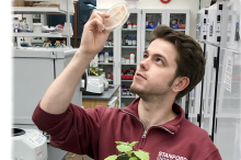 Photo of a male graduate student holding up a petri dish in one hand, with a small plant held in the other.