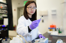 Photo of postdoctoral scholar Chong Liu examining a carbon-amidoxime electrode in the laboratory.