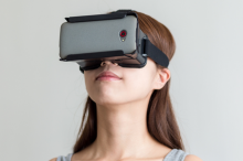Photo of a woman wearing a virtual reality headset in front of a gray background.
