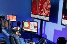 Photo of two surgeons sitting in armchairs, wearing virtual reality headsets in front of large monitors displaying surgery images.