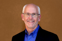 Photo of Dr. Paul Yock standing in front of a brown background.
